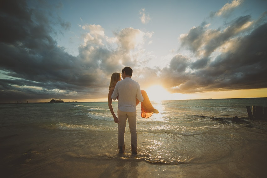 Man carrying his fiance into the sunset lit sea.