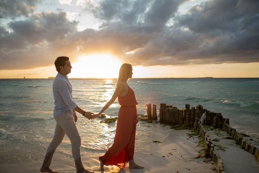 Couple walking on the sunset-lit beach.