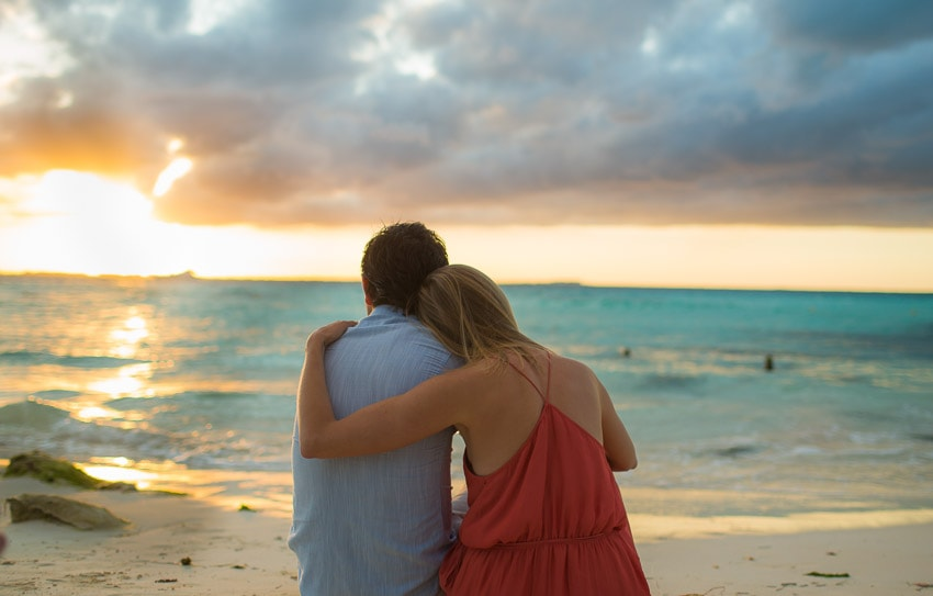 Couple admiring the sun's glow over the Caribbean Sea.