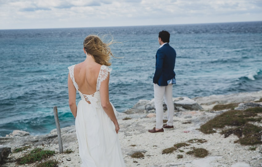 Bride watching her groom stare out into the ocean