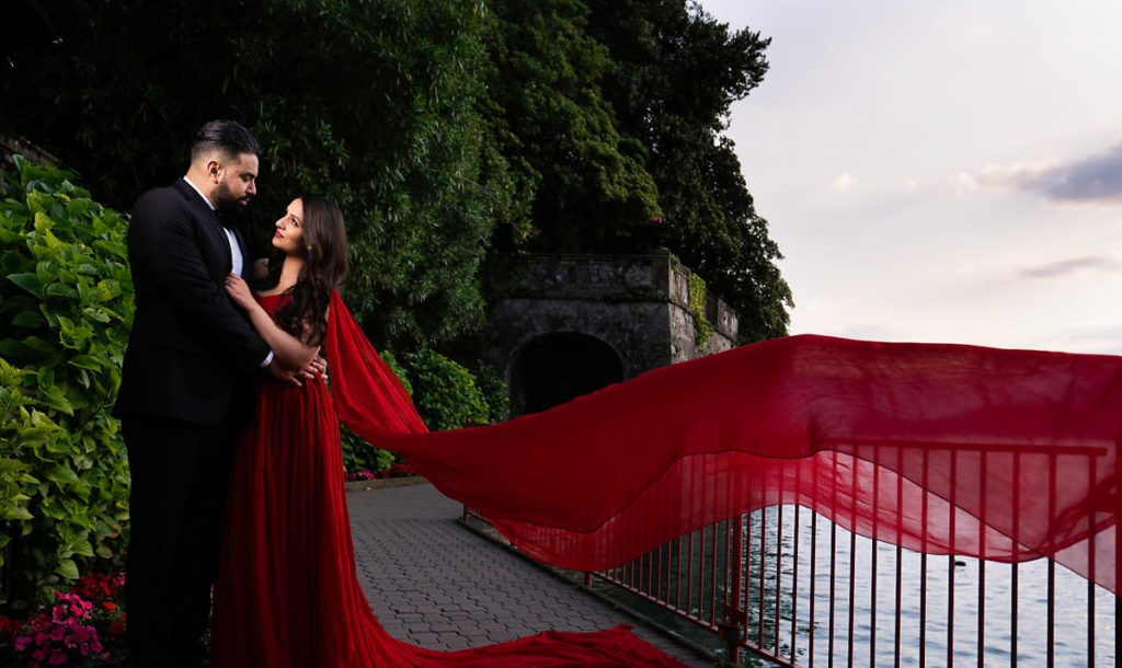 Engagement photo session in Lake Como. Bride in extra long flowy red dress. Lake and Italian alps in the background.