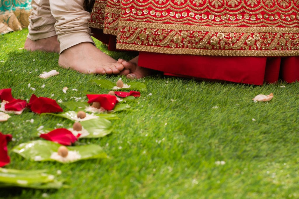 Indian bride and groom play footsies at their ceremony