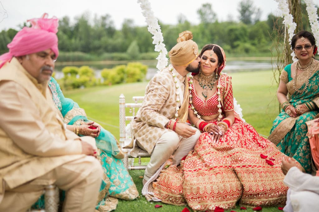 Indian groom gives his bride a kiss on the cheek