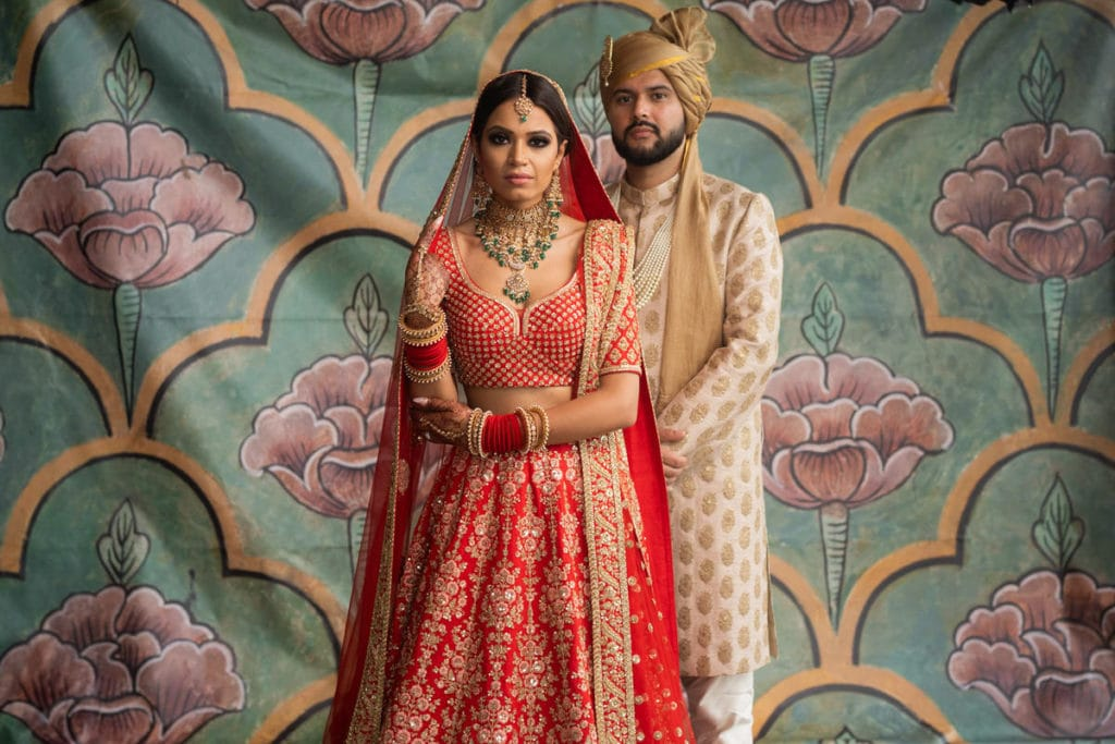 Indian bride and groom pose in their Sabyasachi outfits in front of a Rajashtani backdrop