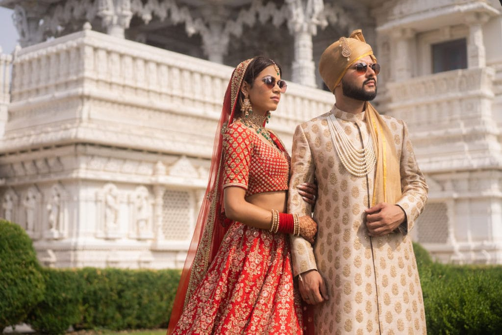 Real Sabyasachi Indian couple pose in front of BAPS mandir Toronto Canada with their shades on