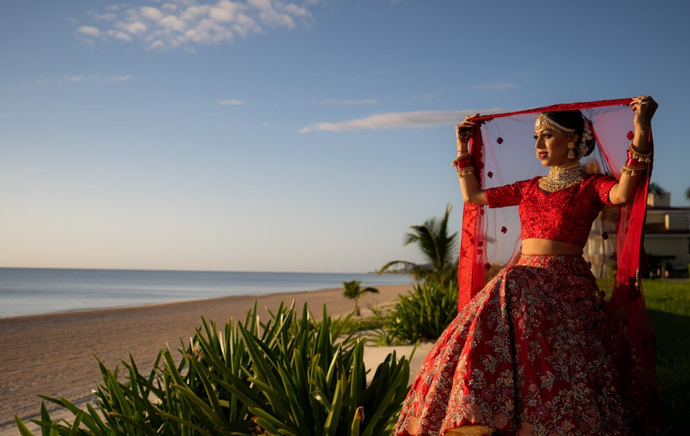 Indian bride in red lehenga getting ready
