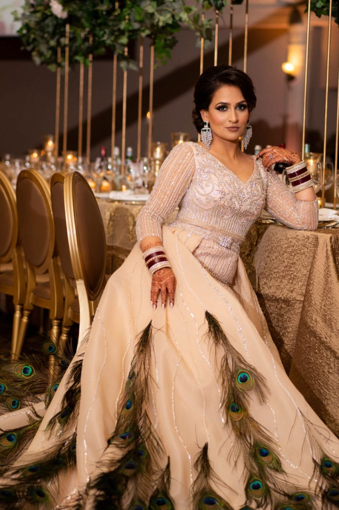Glamorous Indian bride in peacock feather cream gown at the Bellvue manor.