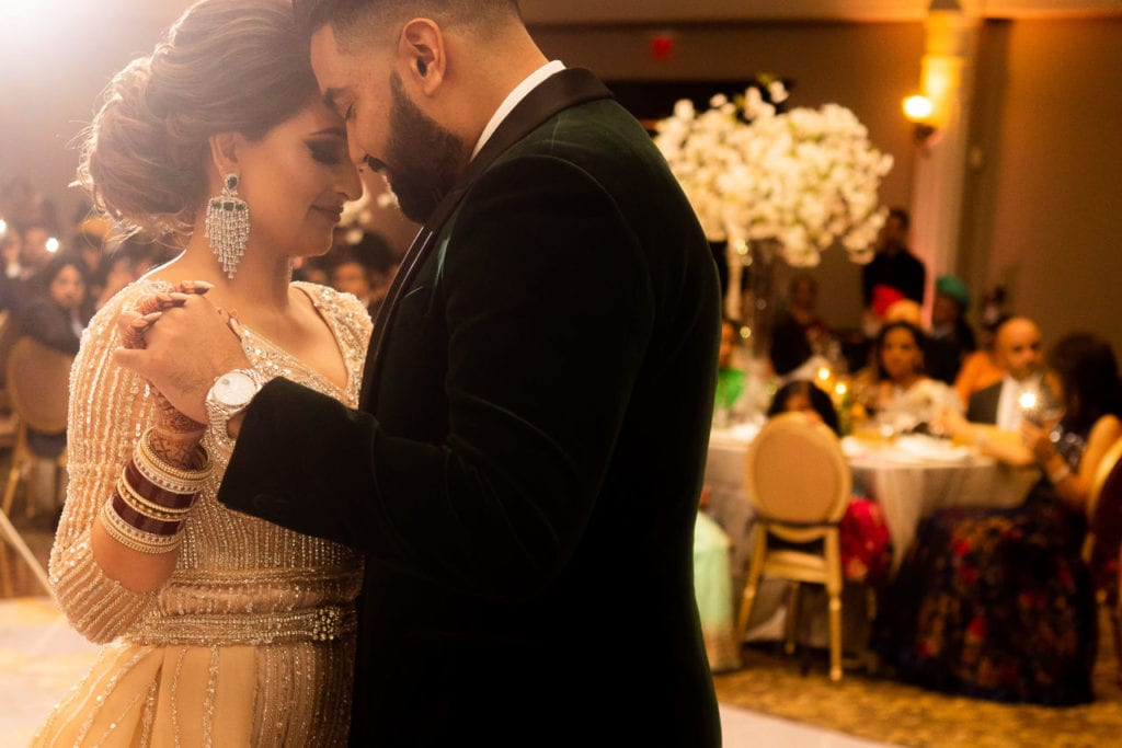 Modern Indian couple at their glamorous reception at the Bellvue Manor, Toronto. Groom in dark green velvet tuxedo and bride in extravagant cream bedazzled long gown with peacock feathers on trail. At their first dance.