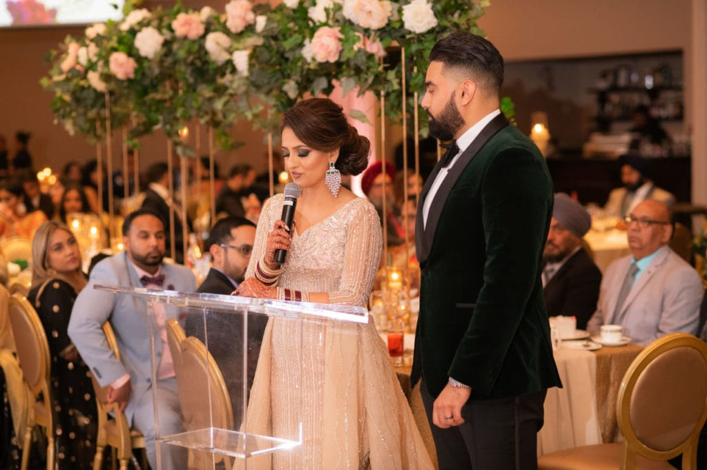 Modern Indian couple at their glamorous reception at the Bellvue Manor, Toronto. Groom in dark green velvet tuxedo and bride in extravagant cream bedazzled long gown with peacock feathers on trail. Couple gives their thank you speech and pop a bottle of Ace of Spade champagne celebrating their happily-ever-after.