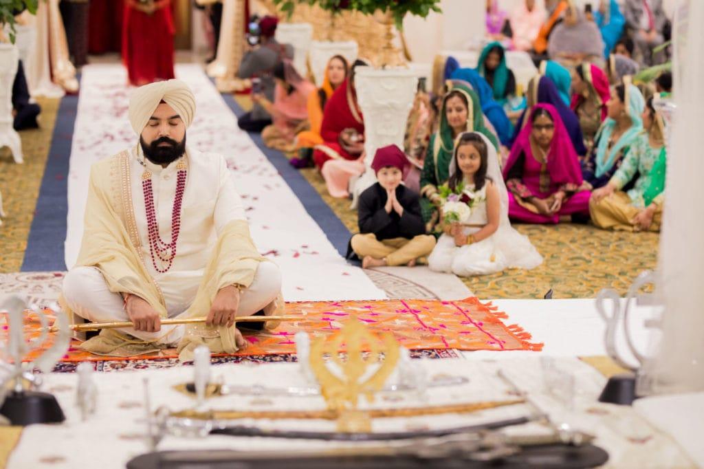 Sikh groom sitting in gurdwara ceremony hall.