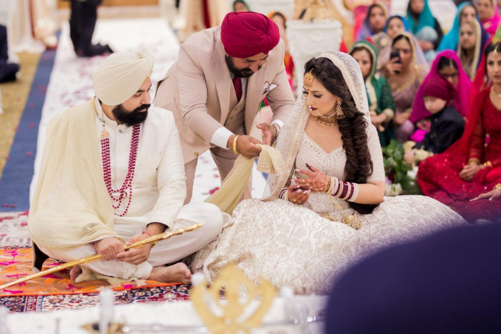 Palla ceremony at Sikh wedding ceremony the Anand Karaj at Nanaksar Gurdwara in Brampton, Toronto. Father-of-the-bride passes her the ceremonial palla to his daughter, the Sikh bride.