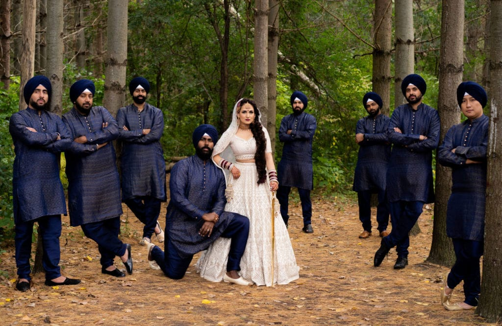 Anita Dongre bride in off-white Indian lehenga with groomsmen/brothers.