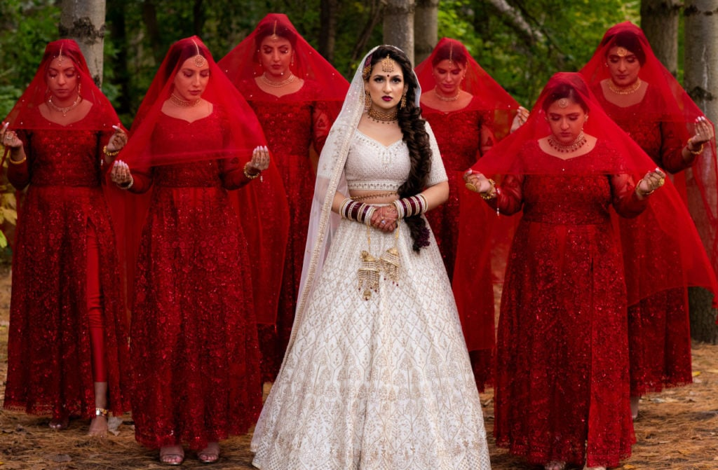 Anita Dongre bride in off-white Indian lehenga with her bridesmais wearing long deep red anarkalis with red net dupattas held over their heads.